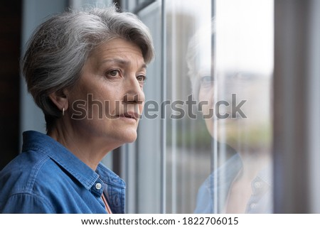 Unhappy elderly Caucasian 60s woman look in window distance mourning or yearning at home. Sad mature grey-haired female lost in thoughts feel lonely abandoned in retirement house. Solitude concept. Stock photo ©