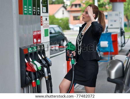 unhappy elegant woman looking price on gas station