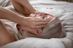 Unhappy exhausted mature woman with closed eyes lying in bed, touching temples close up, tired older female suffering from headache or migraine, feeling unwell, suffering from insomnia, lack of sleep