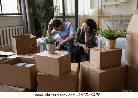 Unhappy frustrated couple sitting on couch with cardboard boxes, eviction, family having problem with dwelling, money or mortgage, worried woman and man lost home, bankruptcy or debt concept Stockfoto ©