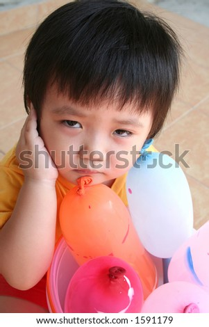 unhappy girl with balloons sitting on the floor
