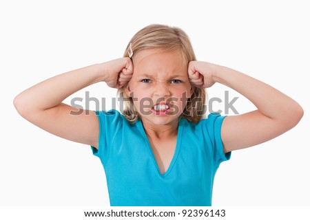 Unhappy girl with the fists on her face against a white background