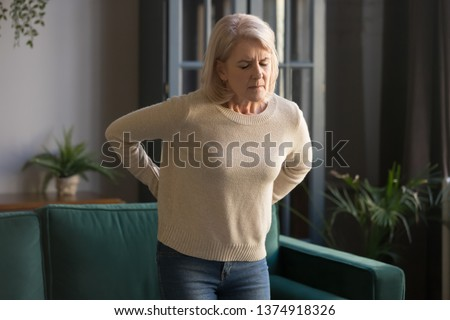Unhappy grey haired mature woman with closed eyes touching, massaging back, tired sad middle aged grandmother suffering from backache, pinched nerve, standing in living room at home alone