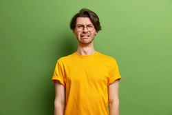 Unhappy handsome Caucasian man cries out in despair feels desperate smirks face wears caual yellow t shirt has melancholic face expression suffers from stress isolated over green background.