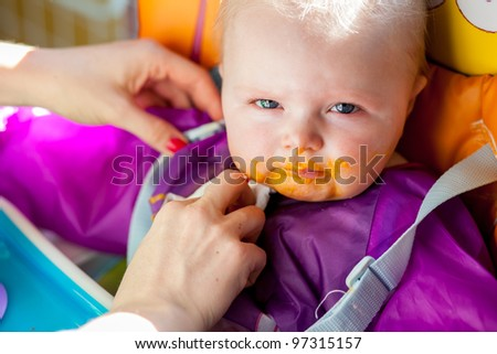 Unhappy infant girl learning to eat solid food