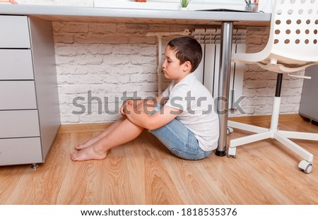 Unhappy kid boy sitting under desk. Teen feeling anxious. Child suffering from loneliness. Junior high age boy being bullied at school. Crying, sad, depressed, stressed, frustrated, overwhelmed Stock photo ©