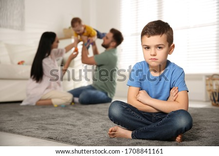 Unhappy little boy feeling jealous while parents spending time with his baby brother at home Stock photo ©