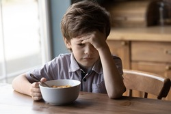 Unhappy little Caucasian boy child sit at table at home kitchen have no appetite for tasty healthy breakfast. Upset stressed small kid refuse to eat delicious organic cereals with milk. Diet concept.
