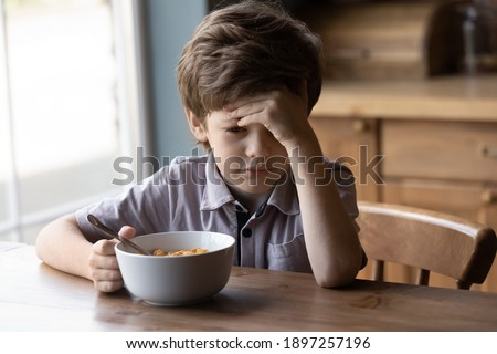 Unhappy little Caucasian boy child sit at table at home kitchen have no appetite for tasty healthy breakfast. Upset stressed small kid refuse to eat delicious organic cereals with milk. Diet concept. Stock photo ©