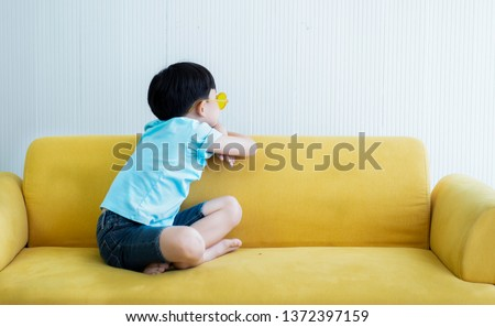 Unhappy little child boy sulk the parents and sitting back on yellow fabric sofa .The boy be pungent the parents sitting back on the couch.