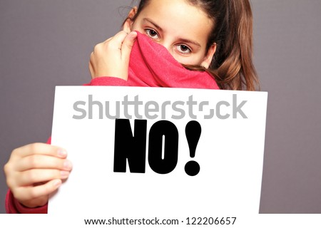 Unhappy little girl hiding behind the collar of her jacket saying an emphatic NO by means of bold type text on a sheet of white paper