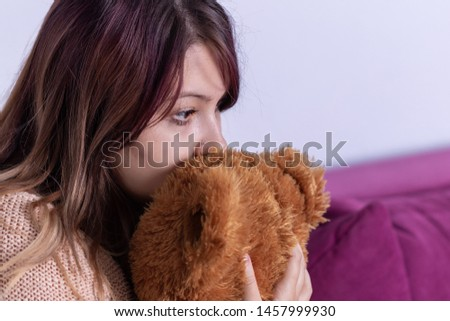 Unhappy lonely depressed woman at home, she sitting on couch and covering her face on stuffed animal, depression concept