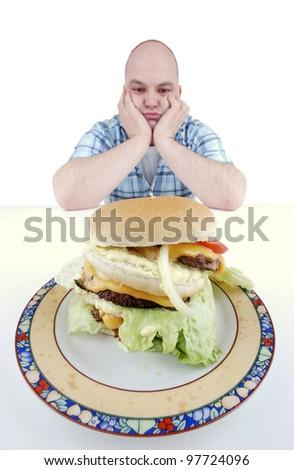 unhappy looking man stares at a big cheeseburger
