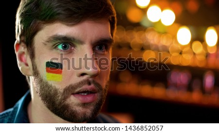 Unhappy male with german flag painted on cheek watching tv, team losing game