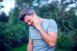 Unhappy man having ear pain touching his painful head outdoor