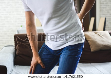unhappy man suffering from backache at home. discus hernia