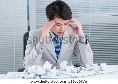 Unhappy manager suffering from headache after long working hours