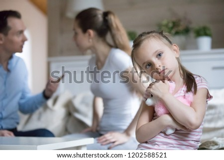 Unhappy married couple and small child at home. Angry husband and wife quarreling arguing talking aloud, focus on sad frustrated little daughter suffers embrace toy looking at camera. Break up concept