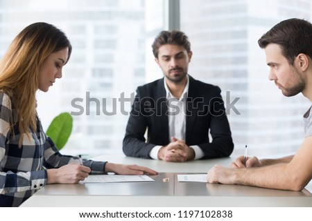 Unhappy married family young couple getting divorced in lawyers office. Husband and wife signing documents on divorce, giving permission to marriage dissolution, breaking up concept. #1197102838