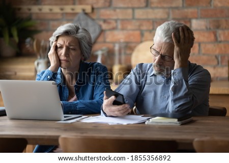 Unhappy mature couple checking financial documents, calculating domestic bills, having problem with money, upset senior man wearing glasses and woman feeling depressed about bankruptcy or debt Foto stock ©