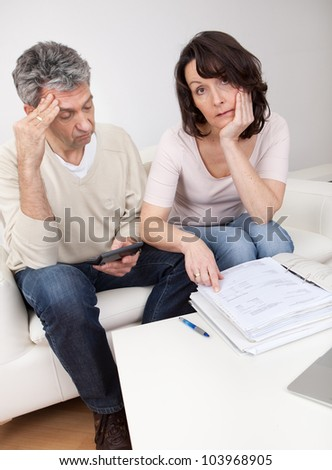 Unhappy mature couple in financial trouble at home