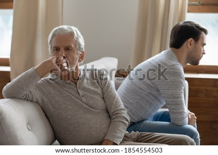 Unhappy mature father and adult son not taking after quarrel, sitting on couch at home separately back to back, upset older grandfather and grandson ignoring each other, two generations conflict Stock photo ©