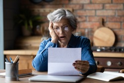 Unhappy mature wearing glasses reading bad news in letter, stressed grey haired female with open mouth looking at paper sheet, sitting at desk, shocked by negative message in correspondence