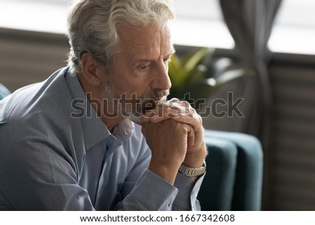 Unhappy middle-aged 60s man sit on couch look in distance thinking mourning at home, sad depressed mature old male feel lonely abandoned pondering remembering past, elderly solitude concept