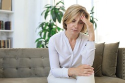 Unhappy middle aged woman sitting on a sofa in the living room.