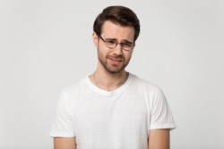 Unhappy millennial man in glasses isolated on grey studio background feel miserable down, sad depressed young Caucasian guy in spectacles crying suffering from relationships problems, stress concept