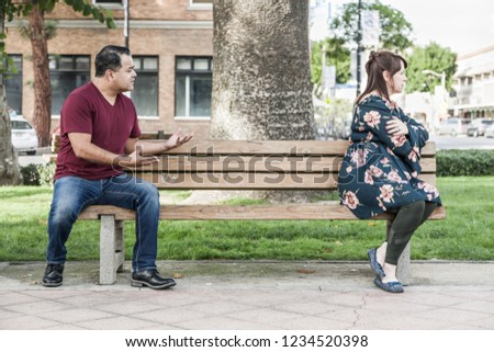 Unhappy Mixed Race Couple Sitting Facing Away From Each Other on Park Bench. #1234520398
