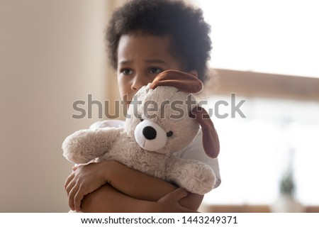 Unhappy mixed race little boy stand hugging stuffed teddy bear feel lonely lacking attention or communication, hurt small biracial kid hold plush toy suffer from loneliness, need parents