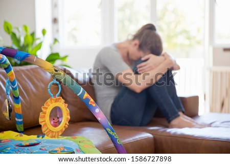 Unhappy Mother Suffering With Post Natal Depression Sits On Sofa Stock photo ©