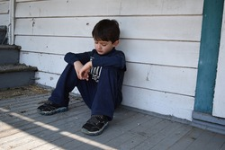 Unhappy neglected child outside home