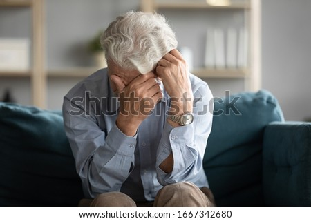 Unhappy old man sit on couch in living room crying mourning or yearning at home, lonely sad middle-aged 60s husband feel abandoned distressed suffer from loneliness or depression, solitude concept