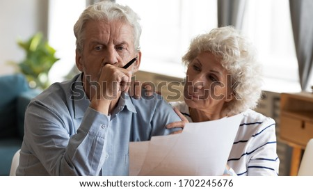Unhappy older couple reading documents, checking domestic bills, caring mature wife comforting sad upset husband holding debt notification, stressed about financial problem or bankruptcy