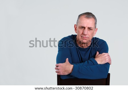 unhappy older man seated looking down #30870802