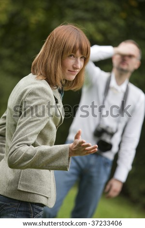unhappy photographer and female model shooting outdoors