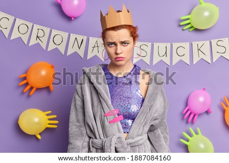 Unhappy redhead woman with makeup looks sadly at camera has bad mood stays at home during coronavirus pandemic organizes domestic party wears paper crown and dressing gown stands offended indoor ストックフォト ©