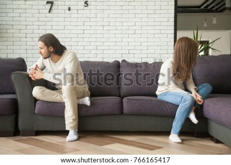Unhappy sad couple sitting apart on couch in living room after quarrel, frustrated man and woman turning their back ignoring having conflict at home, can not find compromise, misunderstanding concept