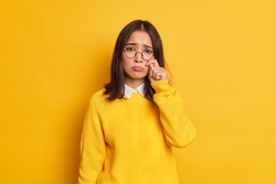 Unhappy sad dejected woman with eastern appearance rubs tears wants to cry feels desperate has problems in life wears round spectacles and casual jumper isolated over vivid yellow background.
