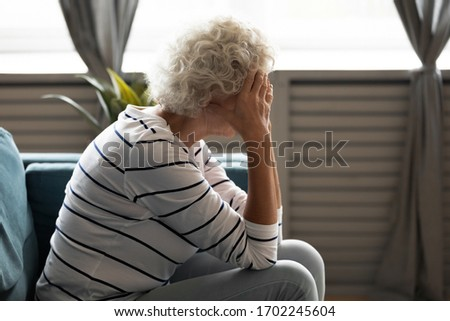 Unhappy sad depressed mature woman covering face with hands, feeling lonely, sitting on couch at home alone, upset frustrated older senior female crying, grieving, worried about problems