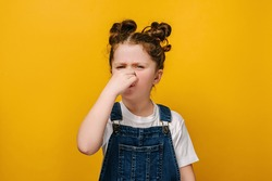 Unhappy sad little preschool girl kid feeling bad and dislike smell and hold nose from funny odor, dressed in white t-shirt, isolated on yellow studio background, six year child looking at camera
