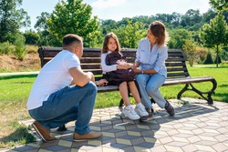 Unhappy schoolgirl in uniform and with backpack and sits with parents on a bench in the park and does not want go to school