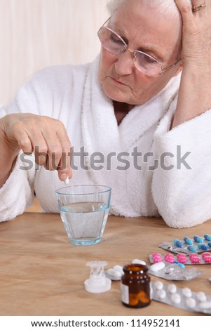 Unhappy senior citizen taking her medication - stock photo