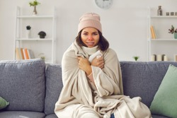 Unhappy sick woman in hat and blanket suffering from cold at home, looking at camera, freezing, complaining to eHealth doctor via Skype, Zoom or FaceTime video call, telling about flu fever symptoms