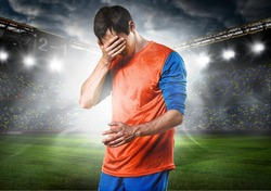 unhappy soccer or football player with palm on his face on stadium