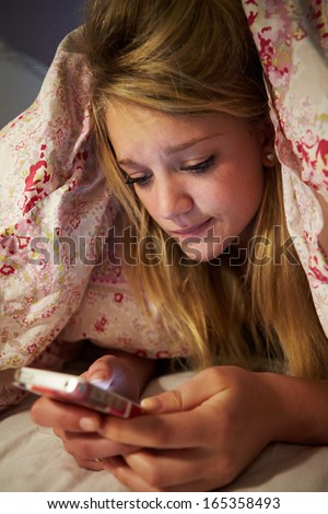 Unhappy Teenage Girl Sending Text Message Whilst Lying In Bed