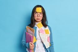 Unhappy tired Asian student concentrated above has sad expression wears spectacles for vision correction holds folders papers stuck with paper clips isolated over blue background learns formulas
