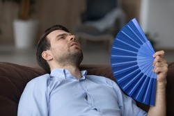 Unhappy tired young Caucasian man relax on sofa at home wave with hand fan suffer from heatstroke. Exhausted millennial male use waver breathe fresh air, struggle lack conditioner indoors.